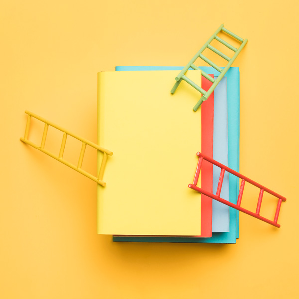bright-ladders-stack-colorful-blank-books-yellow-background